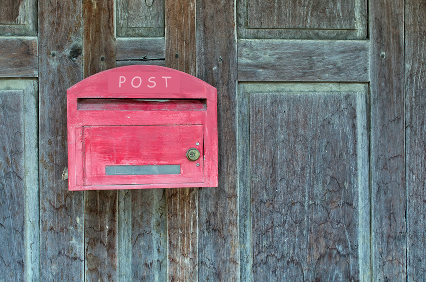 Red wooden mail box on wooden wall.